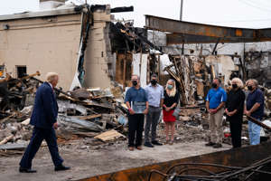 President Donald Trump speaks with business owners Tuesday, Sept. 1, 2020, as he tours an area damaged during demonstrations after a police officer shot Jacob Blake in Kenosha, Wis. (AP Photo/Evan Vucci)