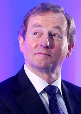 Enda Kenny wearing a suit and tie smiling and looking at the camera: Enda Kenny declined to participate in the gala dinner after the golf competitions. Pic: Niall Carson/PA Wire