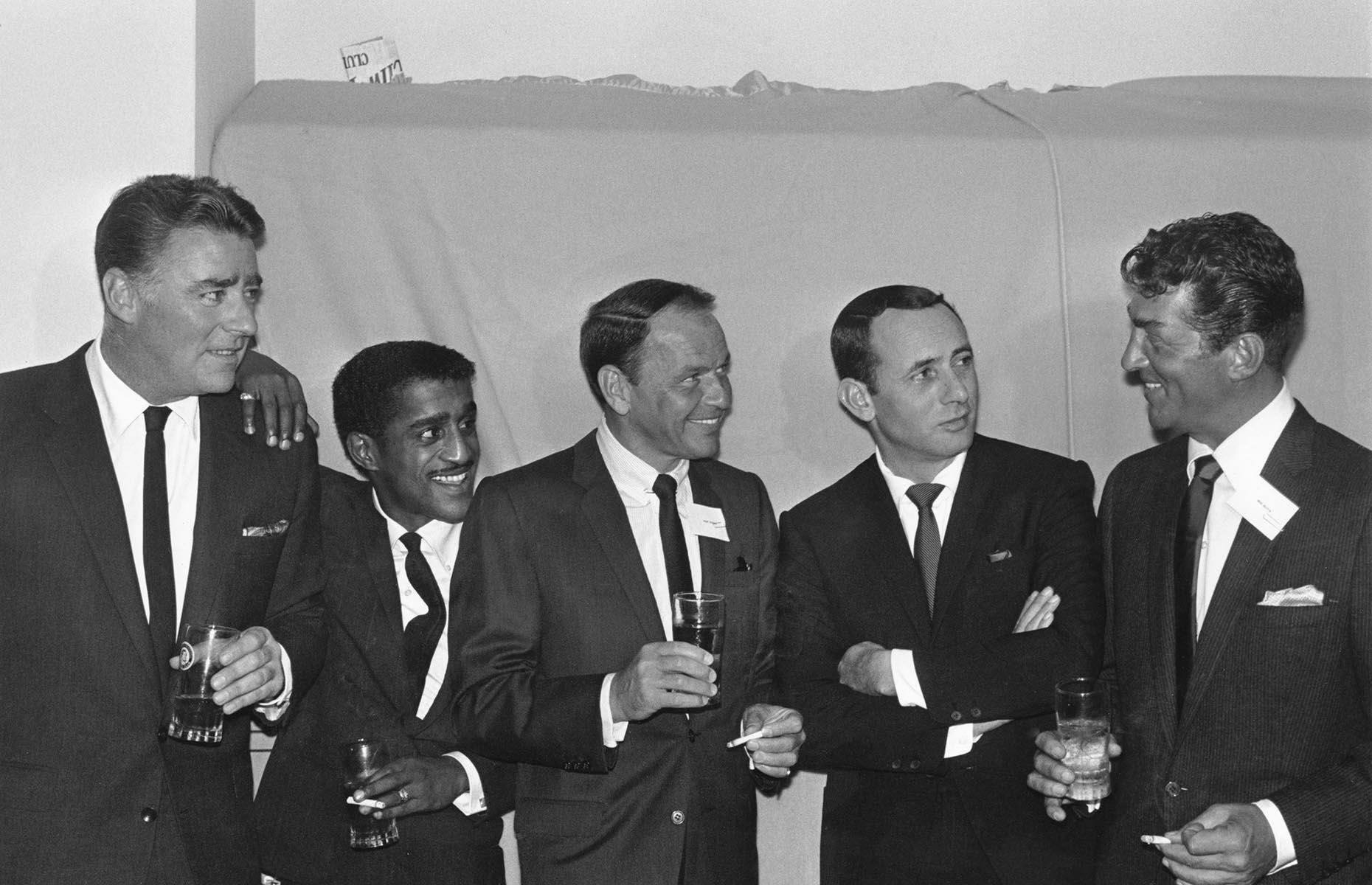 Slide 19 of 34: The Rat Pack (pictured here) are often praised for their desegregation efforts in Las Vegas. When Sammy Davis Jr headlined at the Frontier Casino, he wasn't allowed to stay in the city's hotels, like all Black performers at the time. He wasn't provided with a dressing room and was required to wait outside by the pool between acts. With the Rat Pack's support, Davis Jr later refused to work in any establishment with racial segregation until full desegregation in 1960. When The Moulin Rouge opened in May 1955, it became the first integrated casino in Las Vegas.