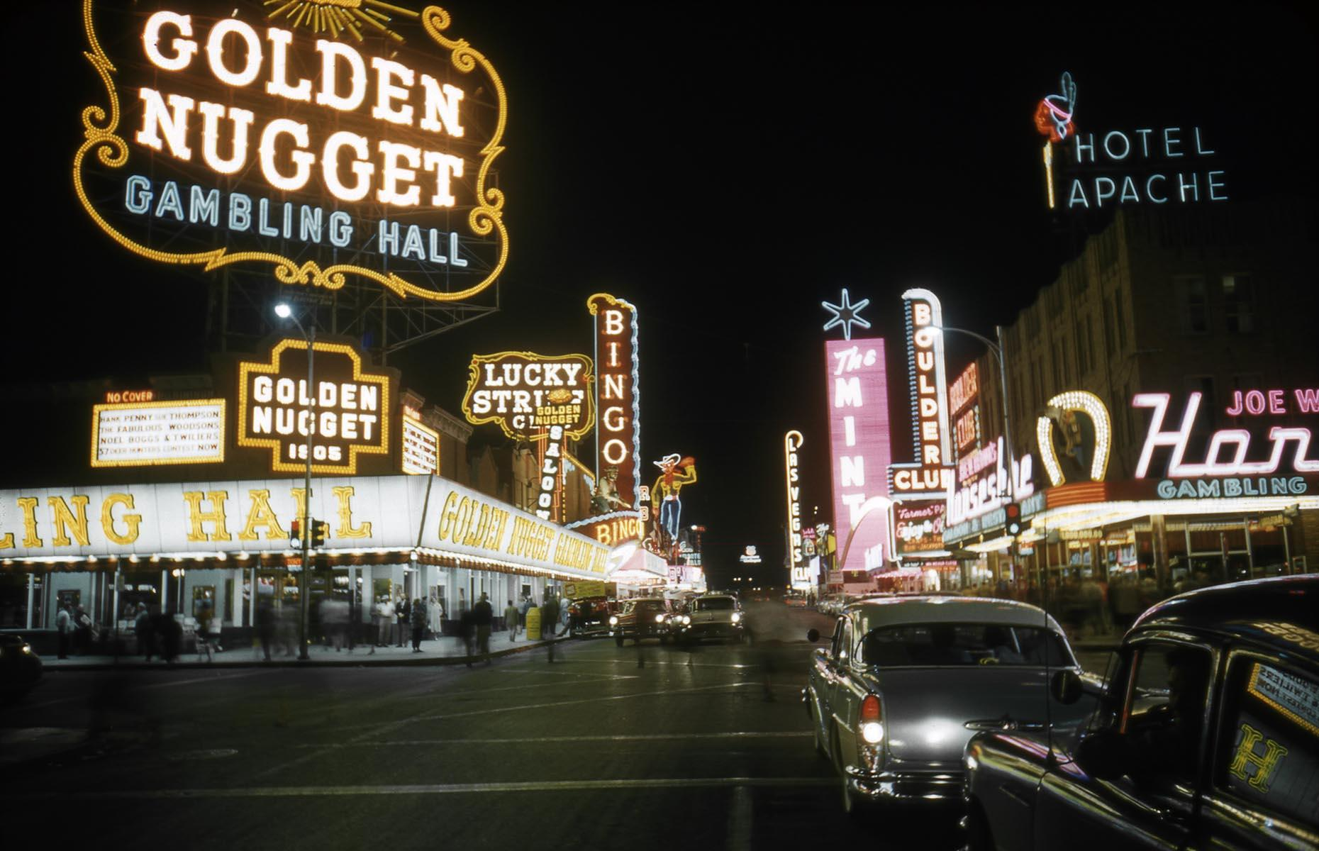Slide 15 of 34: One of the oldest Las Vegas hotel-casinos still around today, Golden Nugget first opened its doors in 1946. Its massive neon sign instantly became an icon of Fremont Street (pictured here in 1958) and along with The Apache Hotel, El Cortez and The Mint, it became known as the Glitter Gulch thanks to the tall neon signs looming over the narrow street. The hotel has been featured on the big screen several times, including Elvis Presley's Viva Las Vegas and Diamonds Are Forever. Now check out these abandoned movie sets time forgot.
