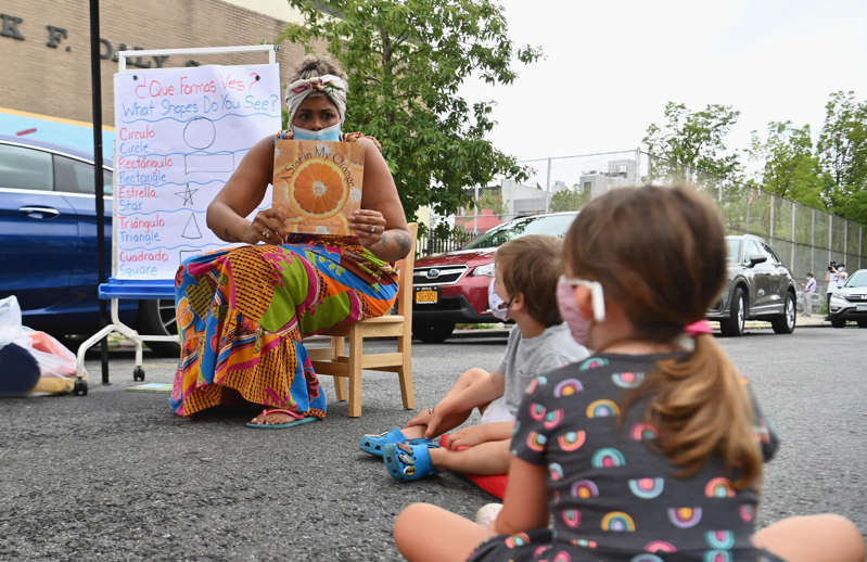 a group of young children sitting next to a baby: A teacher provides an outdoor learning demonstration for New York City schools in front of Patrick F. Daly public school (P.S. 15) in Brooklyn last September. Creative models for outdoor learning are one change that may have staying power after the pandemic.