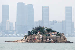 a group of people in a large city landscape: Shiyu, or Lion Islet, part of Kinmen County, one of Taiwan's offshore islands, seen in front of the Chinese city of Xiamen, April 20, 2018. Carl Court/Getty Images