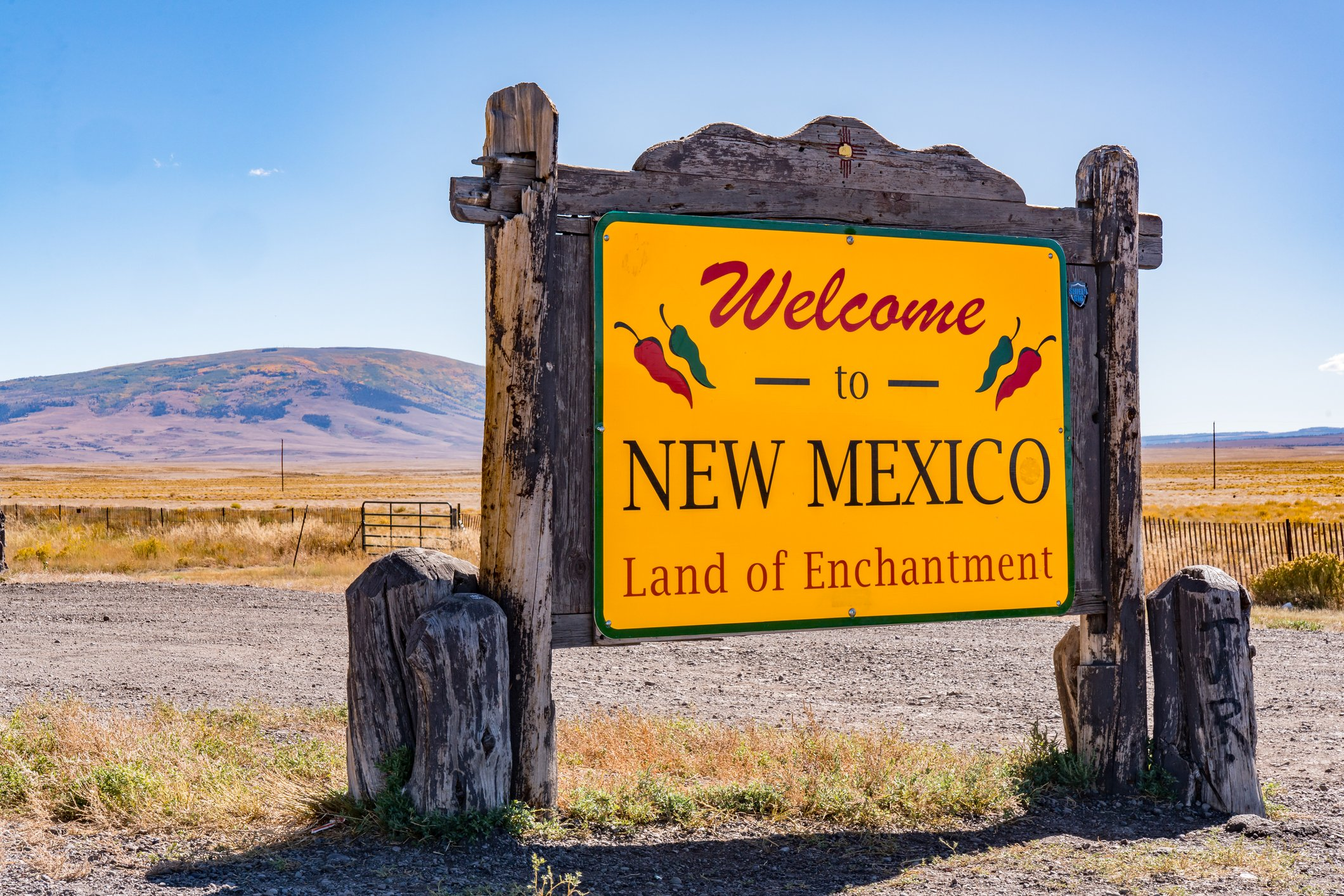 Slide 32 of 51: The sign for New Mexico references the state flag, branding itself with the colors red and yellow.