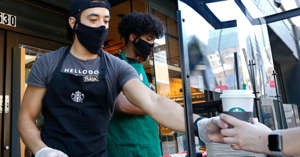 Starbucks shift supervisor Adan Miranda wears a face mask as he serves a drink to a customer while standing behind a plexiglass shield in a booth outside the store in Sacramento, Calif., Thursday, May 21, 2020.