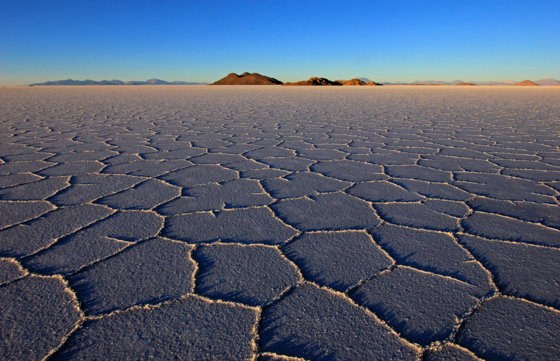 Slide 29 of 36: Salar de Uyuni in southwest Bolivia is the largest salt flats in the world. The high-altitude desert is an extraordinary sight: a crusty expanse of more than 4,600 square miles (12,000sq km) ringed by volcanoes. When the surface is dry, it looks like a patchwork of brilliant white and when wet, the blue sky and clouds above are reflected perfectly. But the salt flats are also resting on half of the world's lithium reserves.