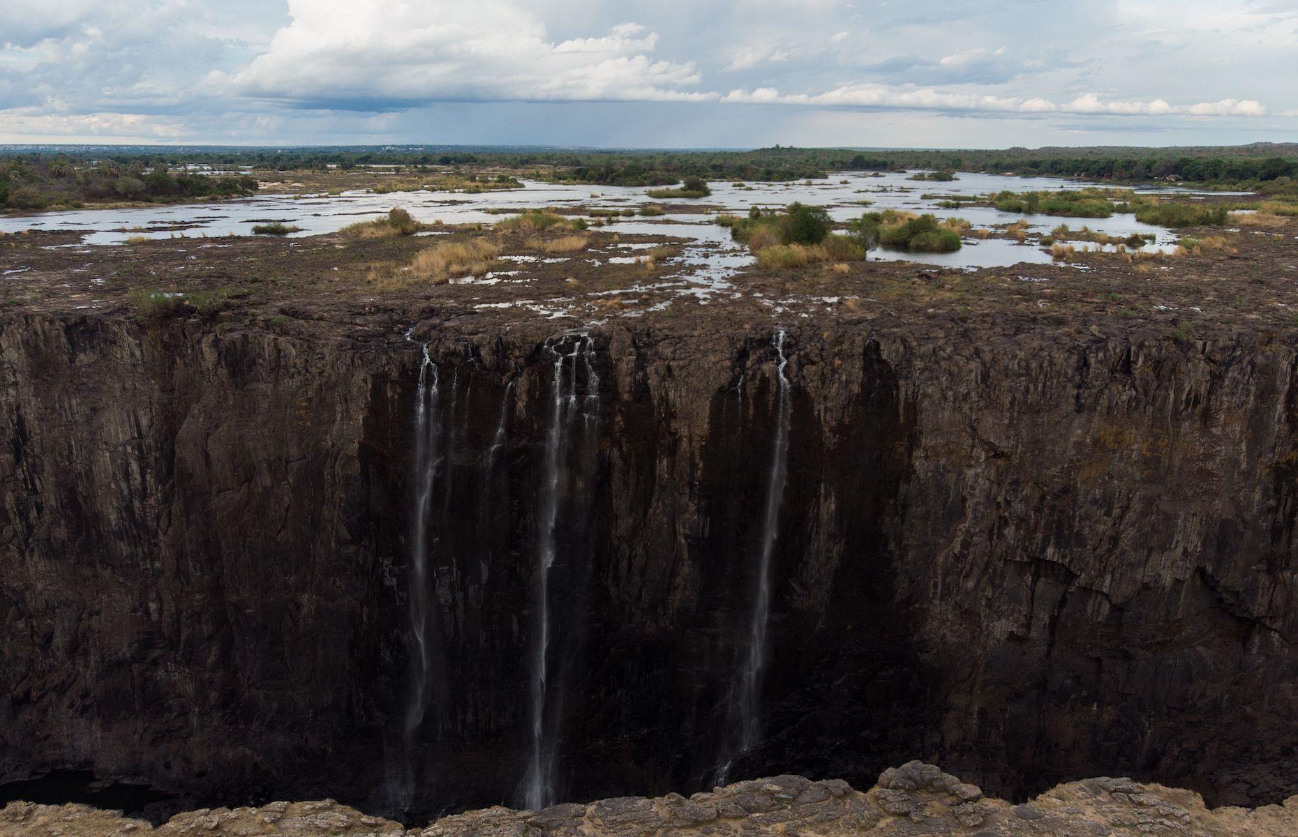 Slide 25 of 36: A Zimbabwe government official told the BBC that low water levels are becoming more frequent and that the average flow over the falls in 2019 was down by almost 50% (pictured here in December 2019). While water levels improved a few weeks later after rains fell in the Upper Zambezi River, the level was still much lower than previous years. Ongoing changes to one of Africa's most famous tourist attractions will have widespread ramifications for both the waterfalls' ecosystems as well as its local economies.