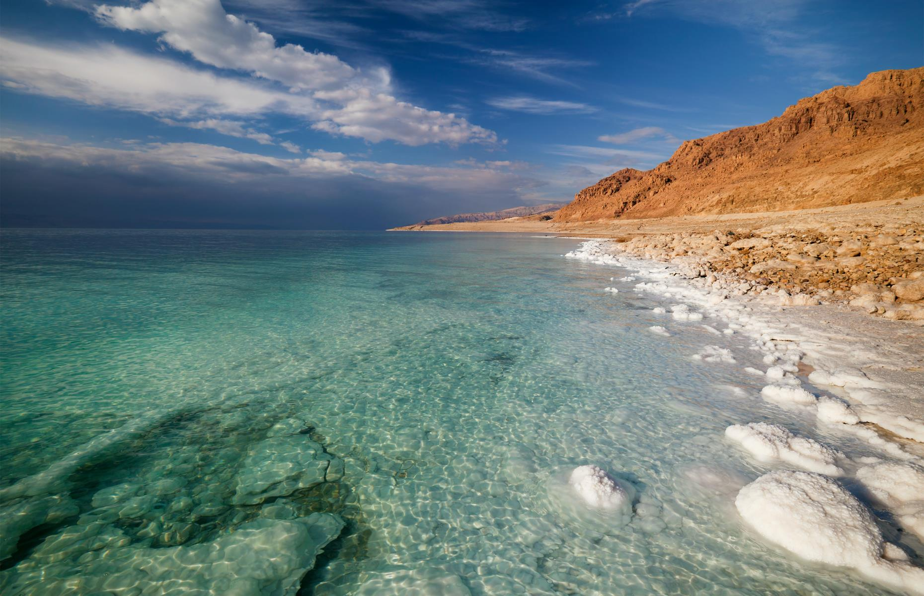 Slide 31 of 36: Bordered by Jordan and Israel, the landlocked Dead Sea is the lowest and saltiest body of water on Earth. However, the sea's buoyant waters are now receding, causing sinkholes to appear. The water level of the Dead Sea is said to be dropping by approximately three feet (1m) a year. About 50 years ago, the Dead Sea covered around 386 square miles (1,000sq km), a level that had been largely constant since records began in the early 18th century. It has now shrunk to around 259 square miles (670sq km).