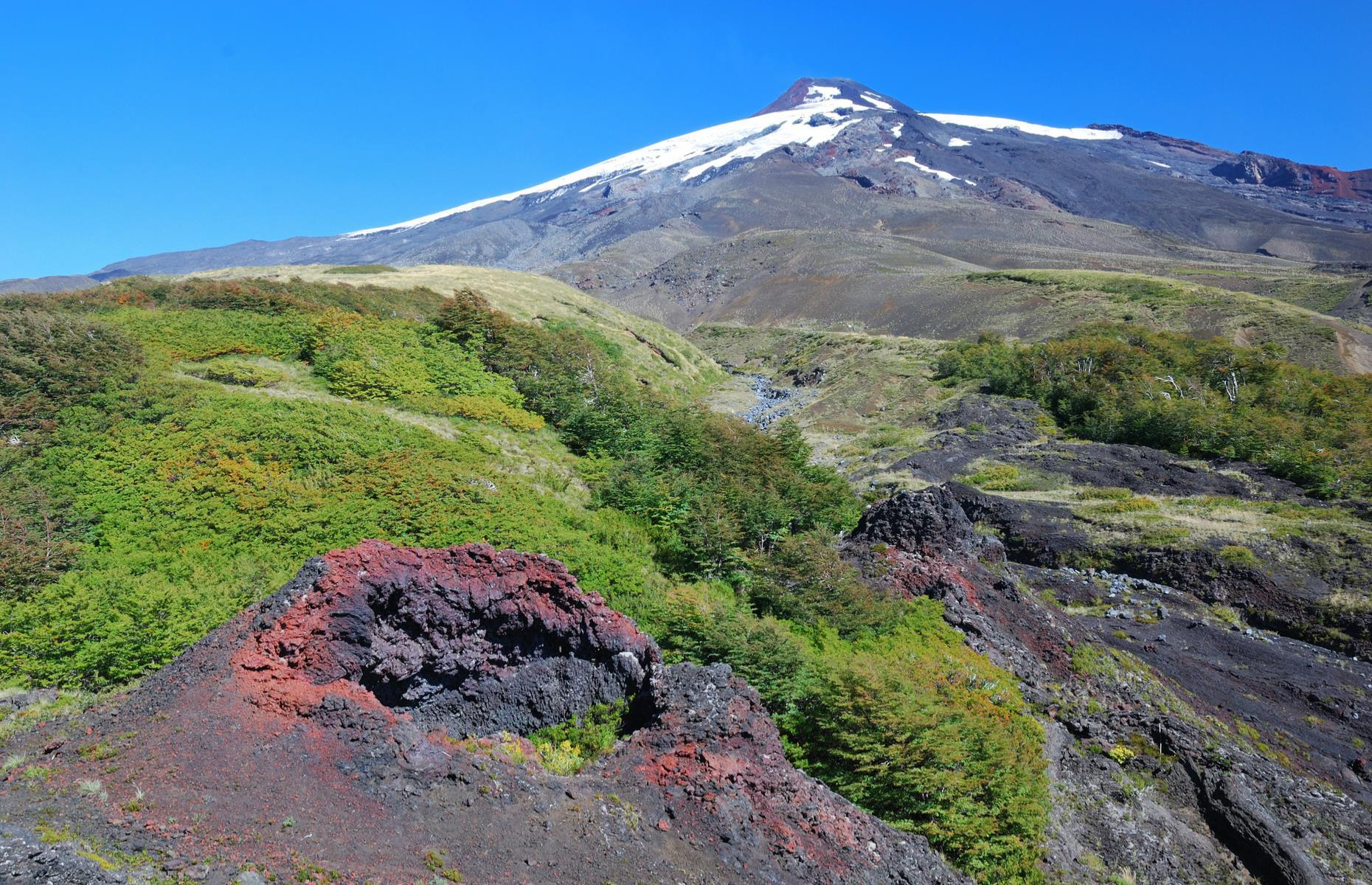 Slide 20 of 41: Villarrica, along with Quetrupillán and the Chilean portion of Lanín, falls inside Villarrica National Park in Chile's central valley. Permanently active, the glacier volcano often has a lava lake at its summit.