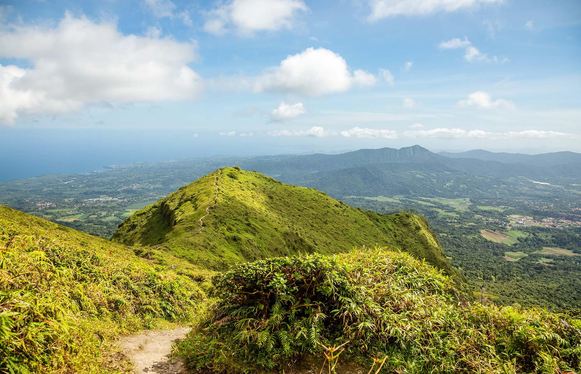 Slide 33 of 41: Also the highest peak in Martinique at 4,583 feet (1,397m), Pelée has several trails to explore the slopes and peak. The views of the bay and its black volcanic sands, when it's not too foggy, are phenomenal. Discover secrets of the world's most beautiful mountains.
