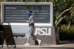 a statue of a person holding a sign: An Arizona State University student walks through Taylor Mall at the school's downtown Phoenix campus on Sept. 9, 2020.