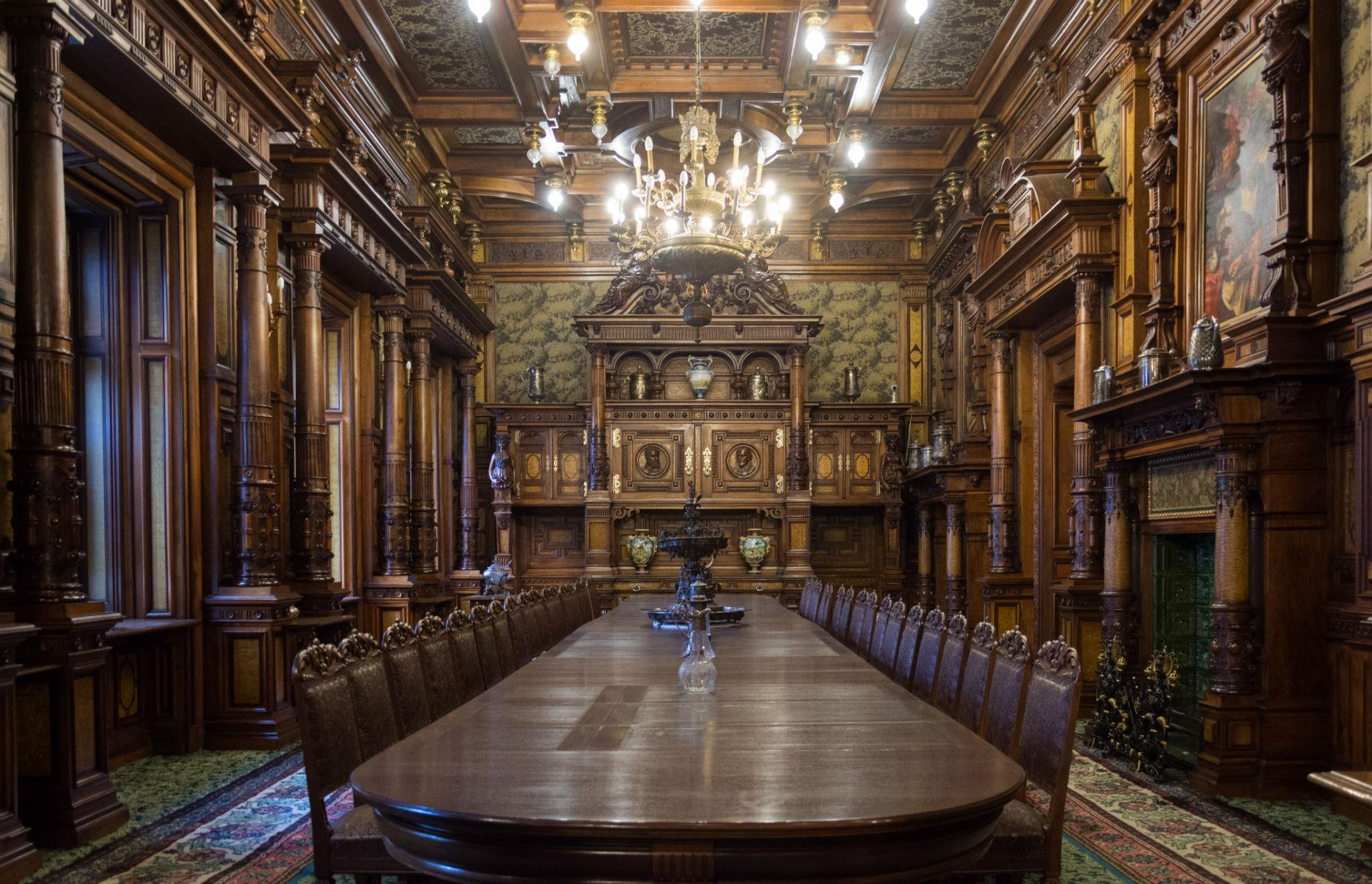 Slide 43 of 61: There are over 170 rooms, brimming with furniture and intricate details. Some have even been decorated to reflect different cultures, from the Florentine Room to the colorful Turkish Parlor. Pictured here is the magnificent, wood-paneled dining room.