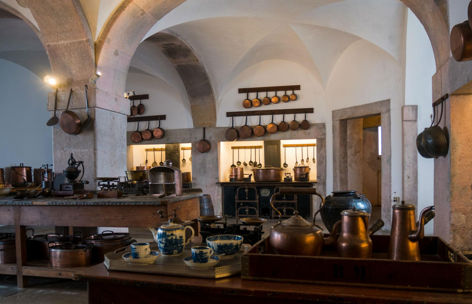 Slide 39 of 61: This photo shows the palace's kitchen, and offers a hint of the scale of preparation needed to keep the castle's royal inhabitants happy. The property is hugged by forested grounds, studded with decorative ornaments and crisscrossed with leafy cobbled walkways.
