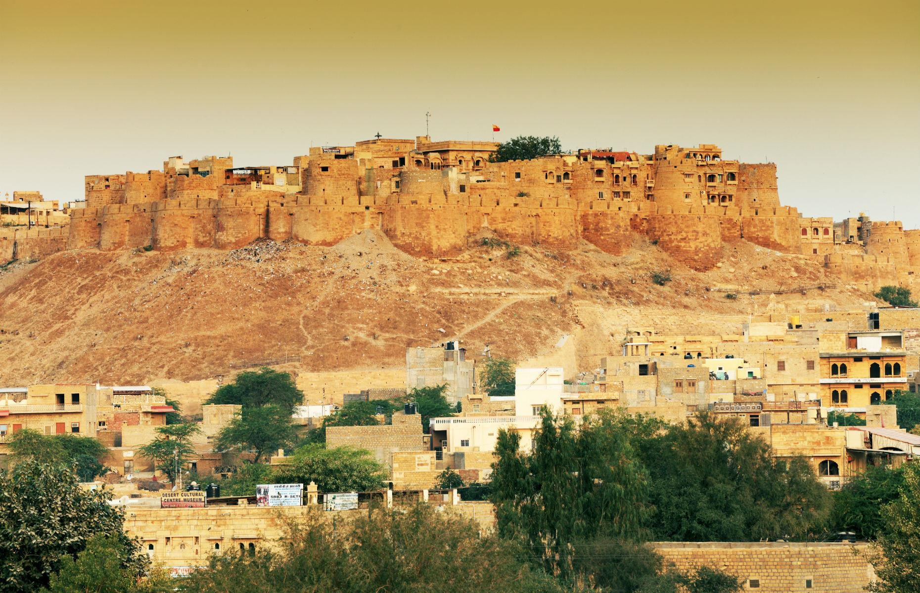 Slide 46 of 61: Jaisalmer fort was constructed in 1156 and, designed to baffle intruders, its yellow sandstone expanse means it's impressively camouflaged. It blends seamlessly with the surrounding Thar desert, especially when the sun sets.