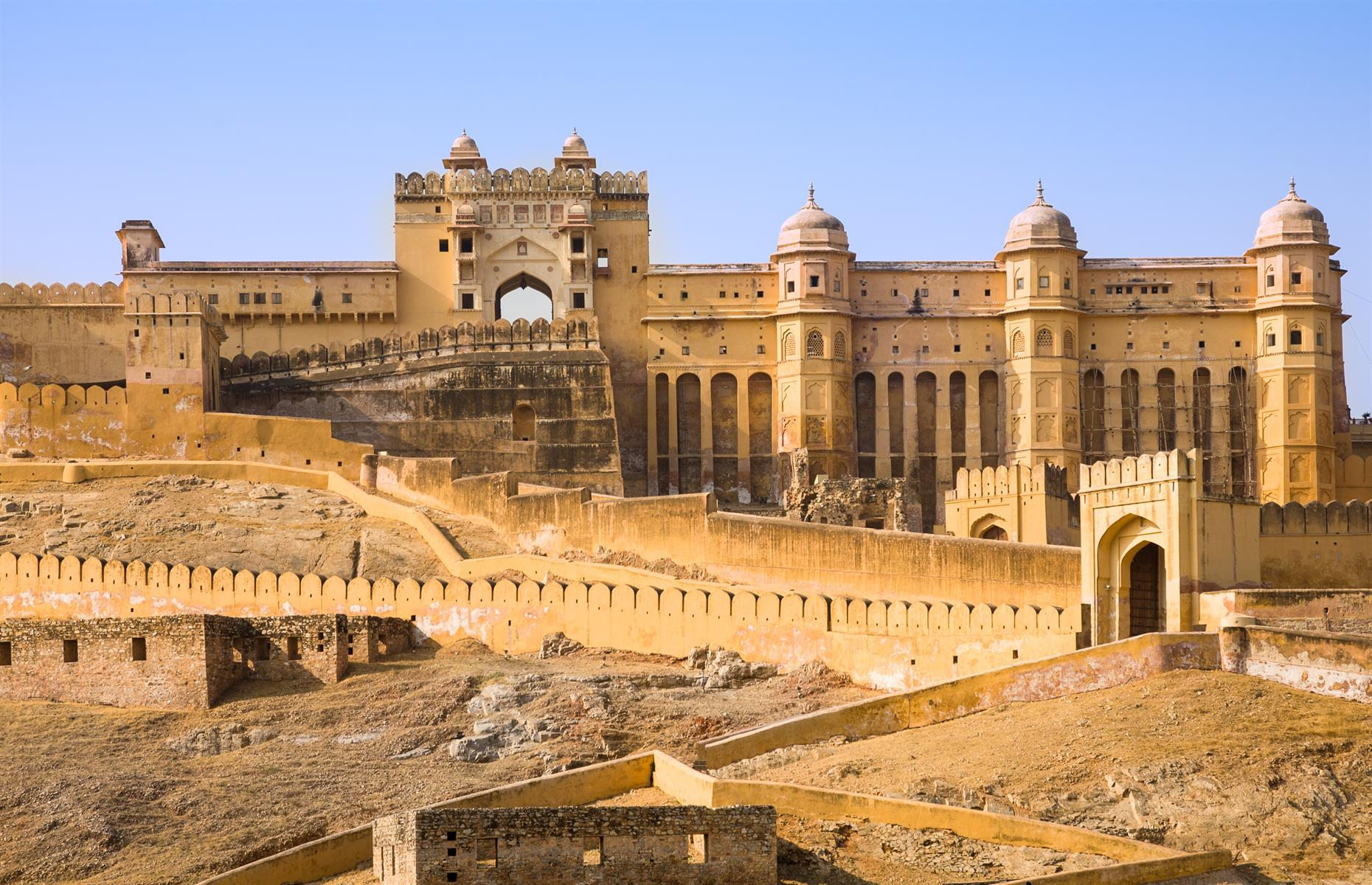 "Slide 26 of 61: Perched on a hill, Amer Fort dwarfs the small town of the same name that lies below. Jaipur – around eight miles (13km) away – is known as the ""Pink City"" and this fortress, built entirely of red sandstone and marble, is typical of the region's style."