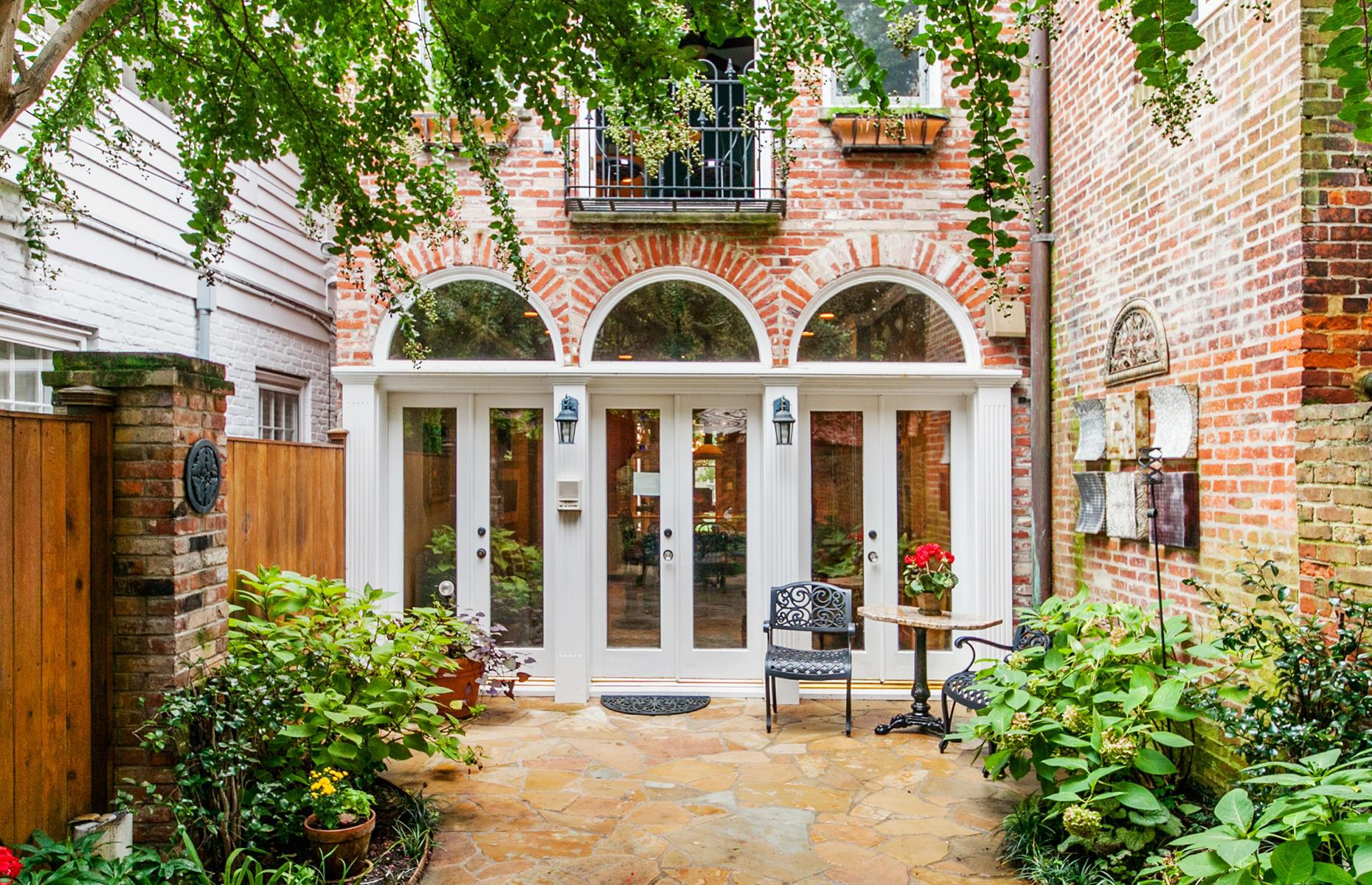 Slide 48 of 52: Located in the beautiful Old Town of Alexandria, just steps away from the Potomac River, this striking home is a country cottage meets Victorian estate. The three-bedroom townhouse has lots of original details like tall ceilings, heart pine flooring and antique furnishings throughout. Outside, there's a serene garden surrounding the property.