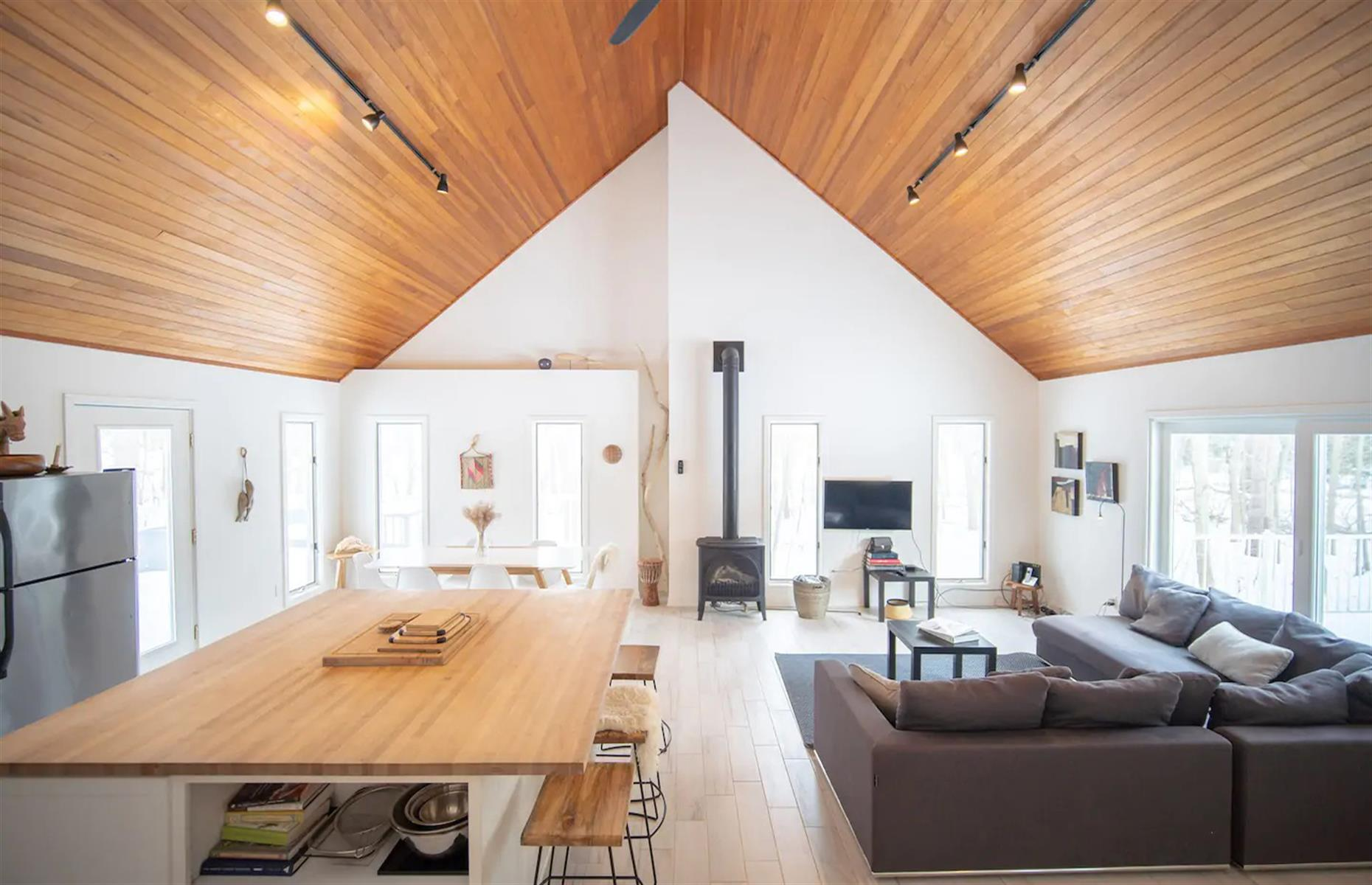 Slide 24 of 52: A calming break awaits at this cottage by Lake Michigan in Holland. The five-bedroom home is within walking distance of James Street beach and conveniently located for exploring the rest of the area. Inside, the stylish interior is flooded with natural light. Pull up a stool at the modern kitchen island for lazy brunches and intimate dinners.