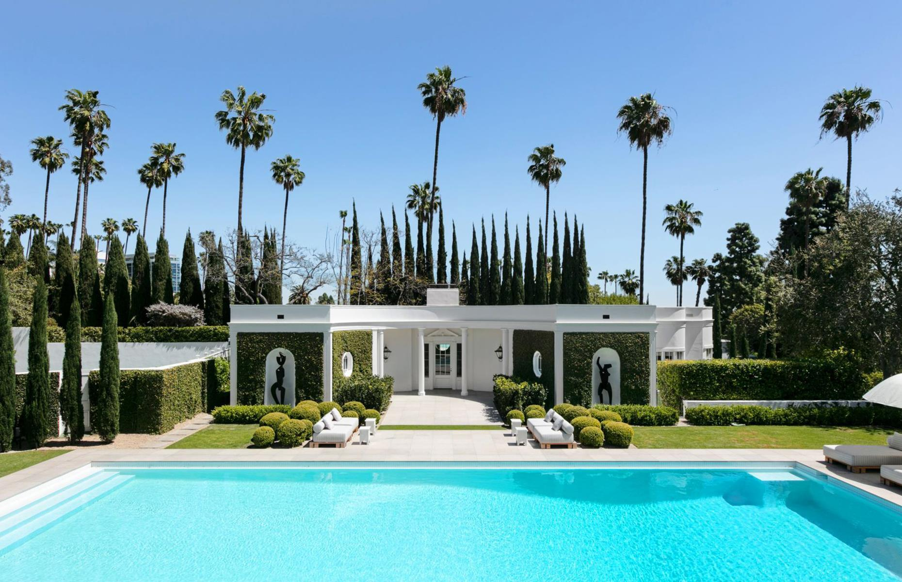 Slide 6 of 52: This mid-century masterpiece is perfect for spending your vacation living like a film star. Statues flank the arched entrance, a library opens to a records room and palm trees soar over the private pool and sculpture garden. Just minutes from the legendary Sunset Boulevard, the villa has seven bedrooms as well as a home cinema and private tennis court.