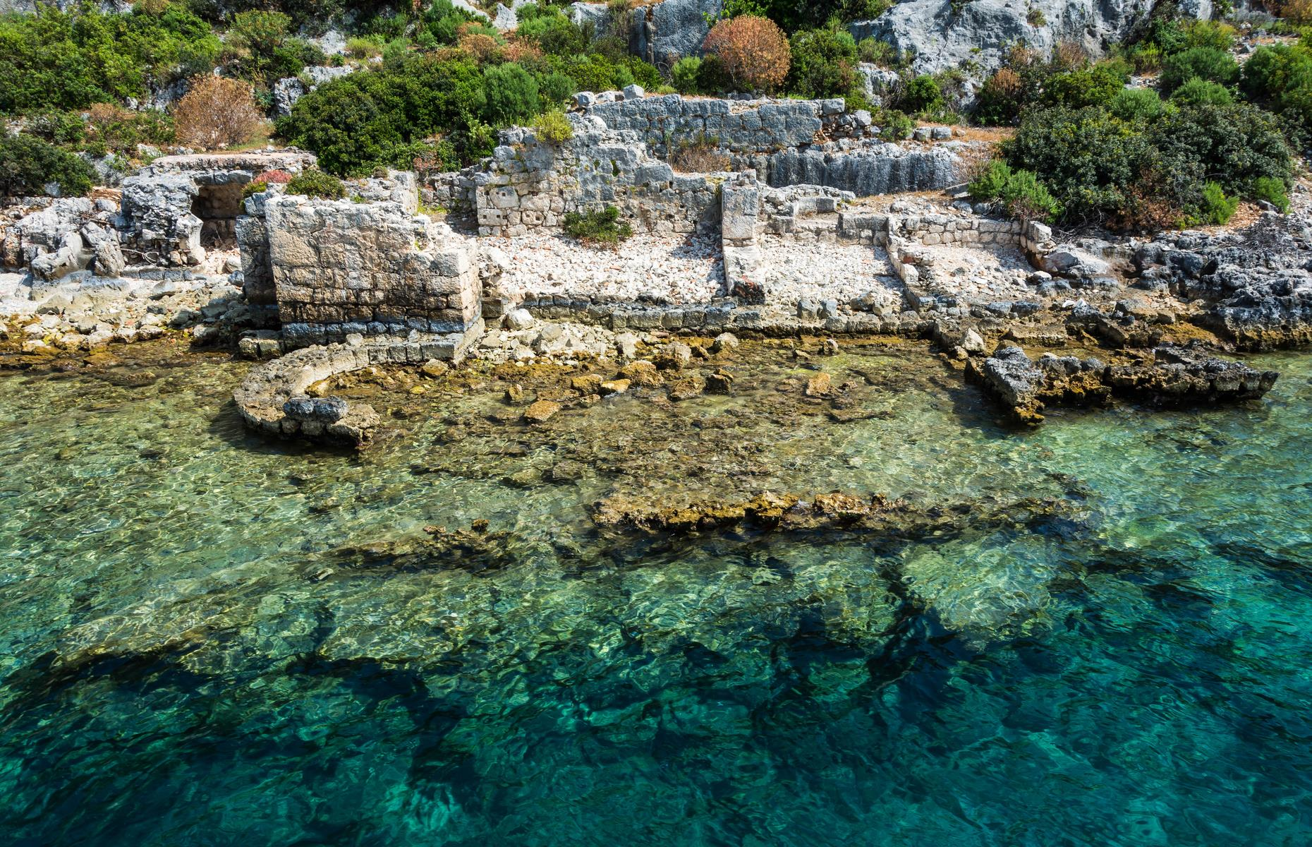 Slide 22 of 25: The crumbly ruins and stone structures of this sunken city peep tantalizingly above the waves and meander their way into the turquoise-tinged water from the rocky northern shoreline of Kekova, a tiny uninhabited island off the coast of Antalya in Turkey. Simena was a sea-trading post and ancient Lycian settlement believed to date to around 2000 BC.