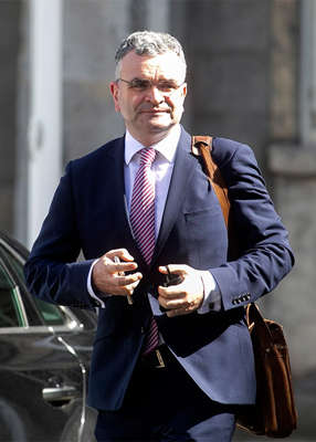 Dara Calleary wearing a suit and tie talking on a cell phone: Dara Calleary didn't even play golf. Pic: Sam Boal/RollingNews.ie