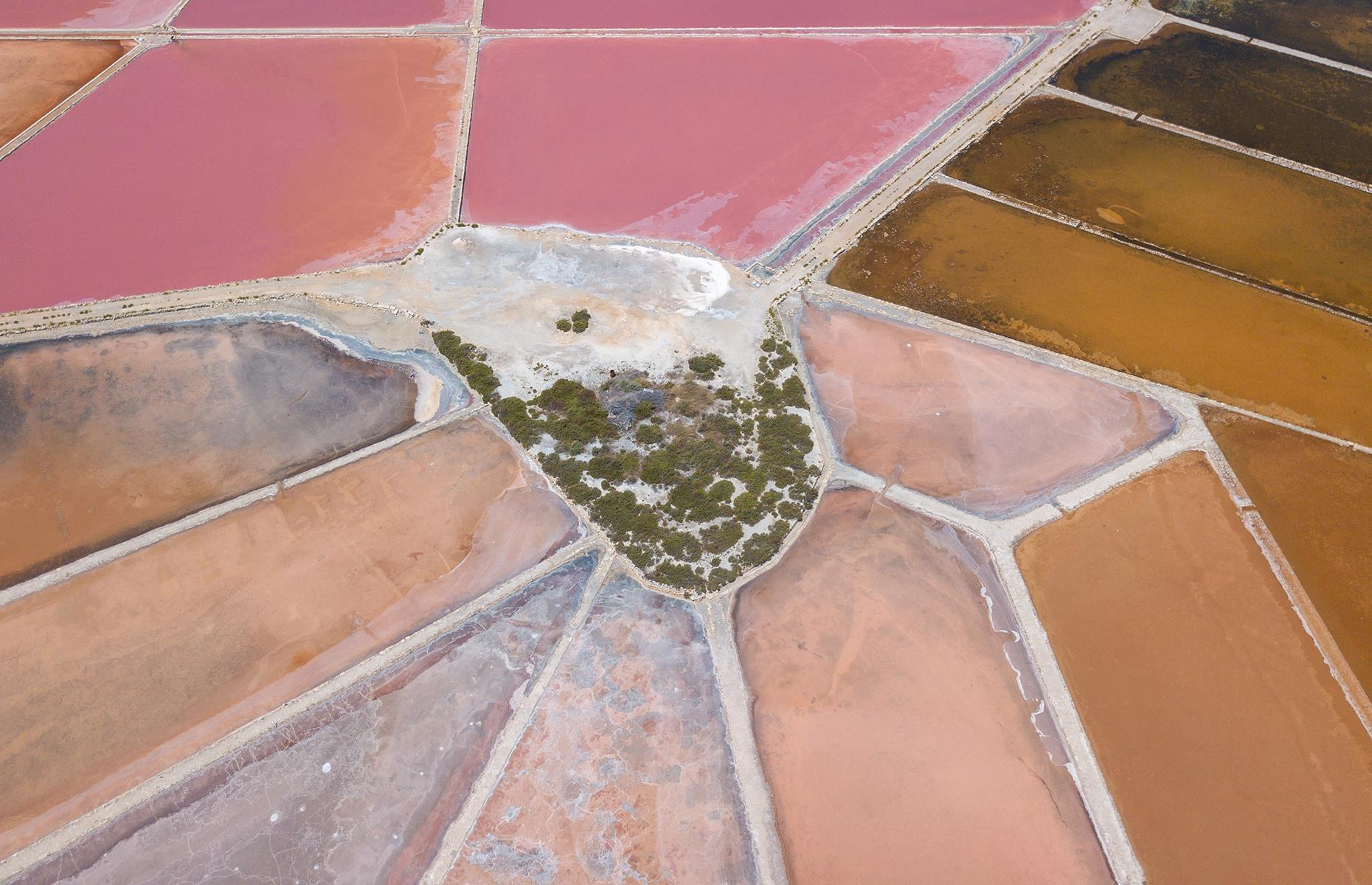 Slide 25 of 43: While it may look like a giant paint palette, this pink landscape is actually made up of salt flats and is situated in the seaside resort of Colonia de Sant Jordi in Mallorca's Ses Salines district. Salt is a major export here and a great source of local pride – a symbol of a salt mound even appears on the area's coat of arms. The colors – earthy pink, deep tan and rich nude – pop when captured from up high.