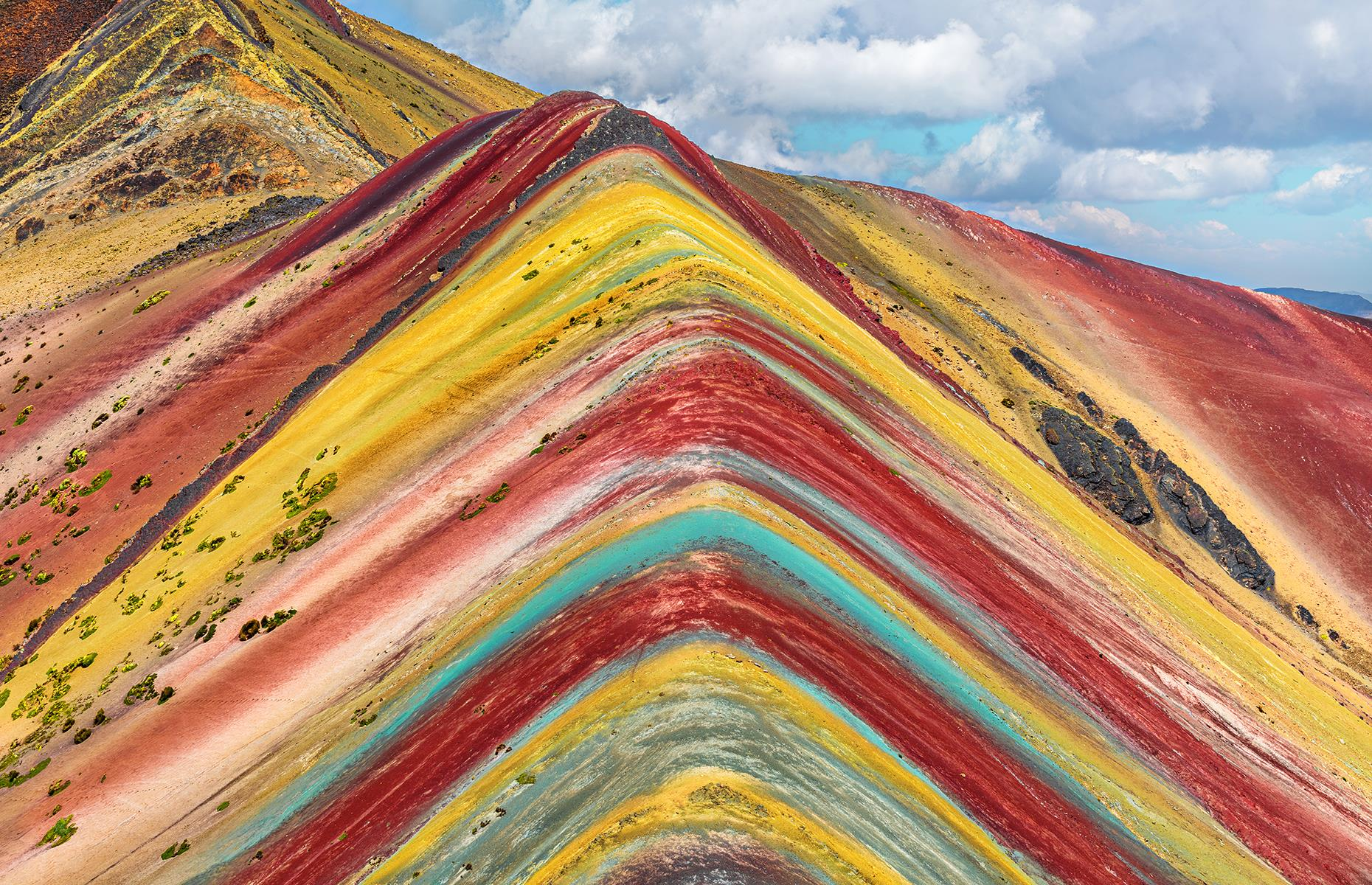 Slide 41 of 43: This multicolored mountain in the Peruvian Andes is not man-made despite what its perfectly symmetrical layers might make you think. The colorful bands, ranging from pink and red to yellow and green, are the result of sedimentary layers forming from mineral deposits over the years.