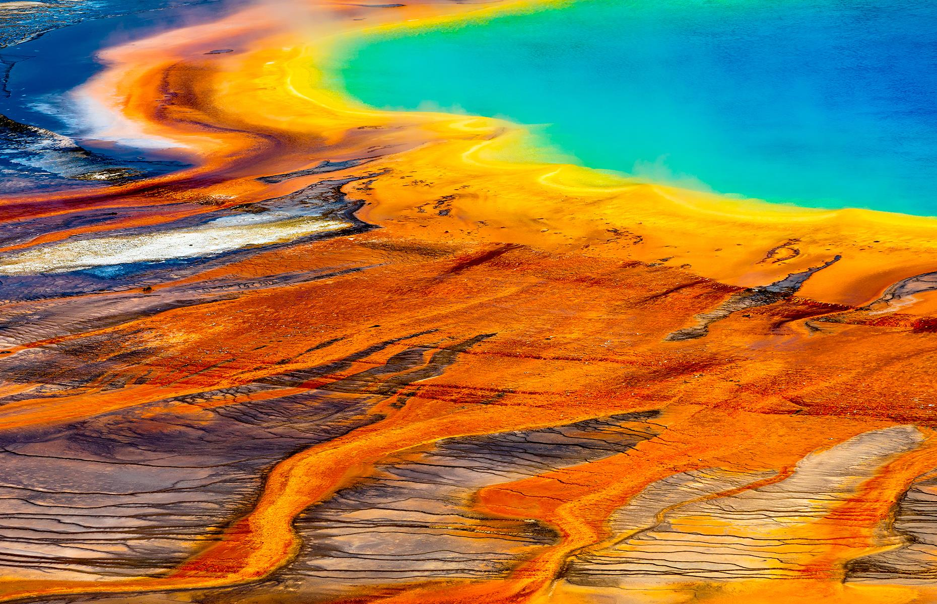 Slide 40 of 43: Yellowstone's most famous hot spring, the Grand Prismatic's vivid blue centeris surrounded by bands of rusty orange, yellow and green, making it look otherworldly. The largest hot spring in the United States and the third largest in the world, Grand Prismatic's water reaches a temperature of around160°F (70°C). Multi-layered sheets of microorganisms called microbial mats give the bands their distinctive colors, that tend to change slightly with the seasons.