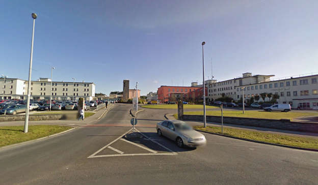 a train is parked on the side of a road: The number of COVID-19 patients admitted to University Hospital Limerick has increased from two to 14 this week as hospitals have sought to deal with the fallout from the cyber attack. Pic: Google Street View