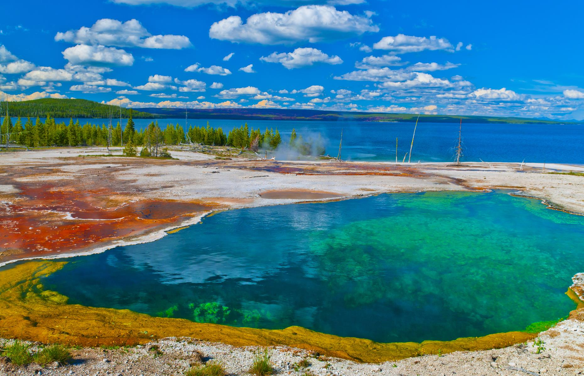Slide 4 of 31: Vast Yellowstone Lake freezes completely in winter and thaws in late spring, but it's strikingly beautiful at any time of year. Bordered by Yellowstone National Park's vivid geothermal springs, its shimmering surface conceals hidden depths....