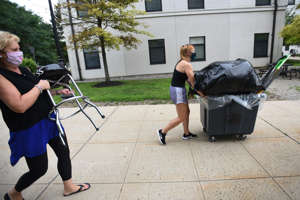 a man and a woman walking down a sidewalk: Amy Horensky of Lebanon, NJ., whose major is in Dance Education, pushes her stuff in a cart helped by her mother Patti as she moves into Willams Hall at Montclair State University in Montclair on 08/13/20.