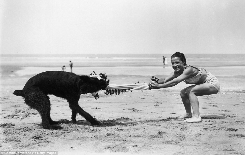 Slide 3 of 25: The coastal commune of Deauville, situated in Normandy, was popular with the upper classes as it was close to Paris. Above, a woman plays tug-of-war with a dog.