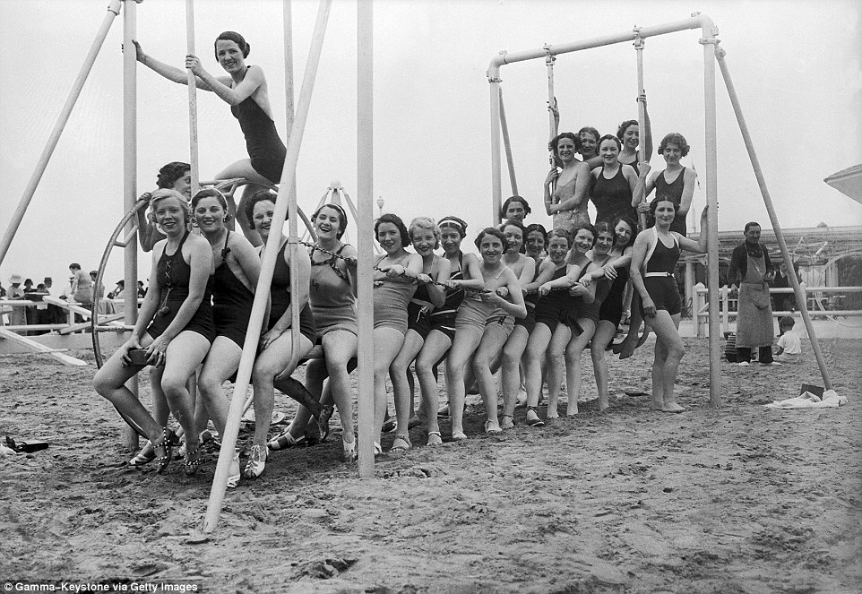 Slide 21 of 25: Girls day out: A group of young women gather and pose around a swing on the beach, pictured in 1936.