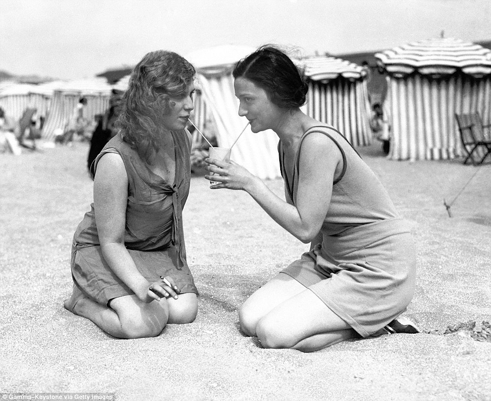 Slide 16 of 25: During the summer holiday of 1929, these two young women were pictured drinking lemonade together, as one hold a cigarette.