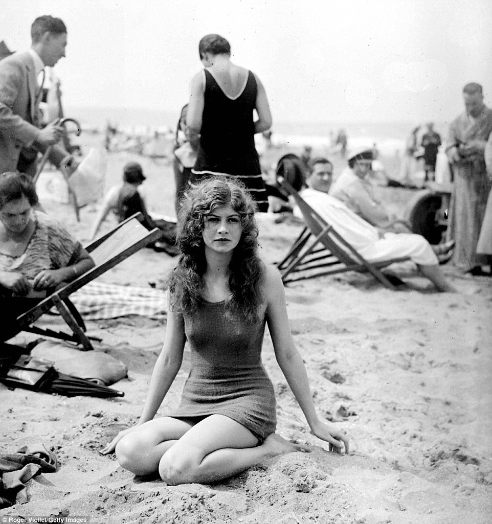 Slide 10 of 25: This picture, taken in the 1920s, show a young woman looking pensive on the beach while surrounded by people on deck chairs.