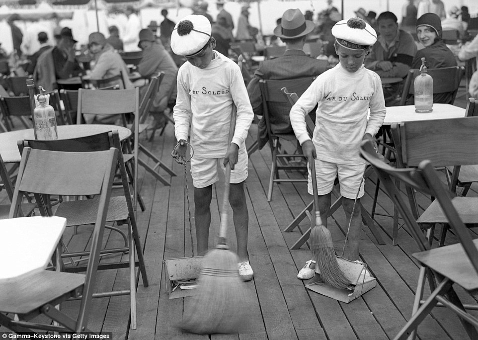 Slide 17 of 25: Two little grooms of the Bar Du Soleil sweeping the floors while the guests look on in 1929.
