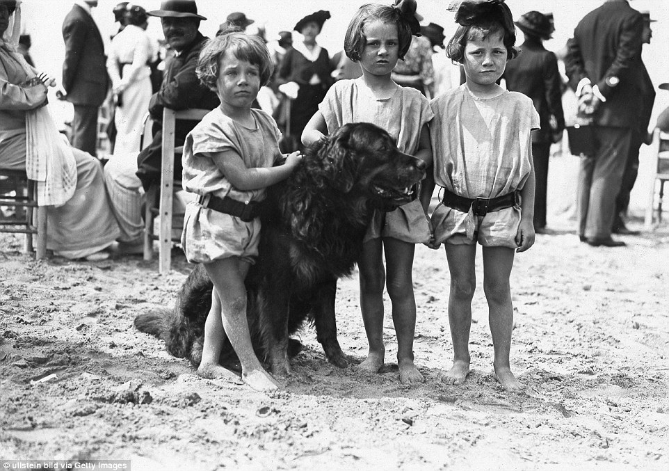 Slide 4 of 25: It's known as the Parisian Riviera and began to be popular from 1860s. Above, three children with a dog at the beach of Deauville in 1913.