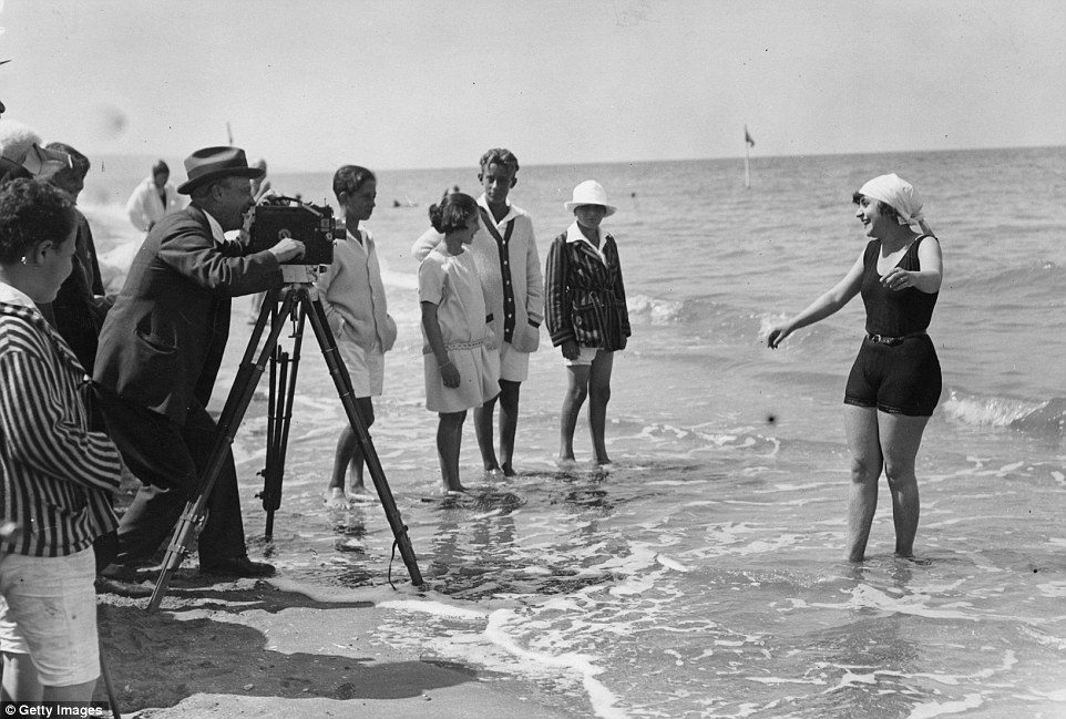 Slide 12 of 25: A woman is being filmed by cine camera, the video recorder of its day, as she paddles in the sea on a beach at Deauville inAugust 1922.