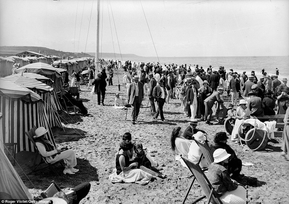 Slide 8 of 25: By 1920, the beaches at Deauville were visibly busy. Many of the people pictured above are still wearing their formal clothing.