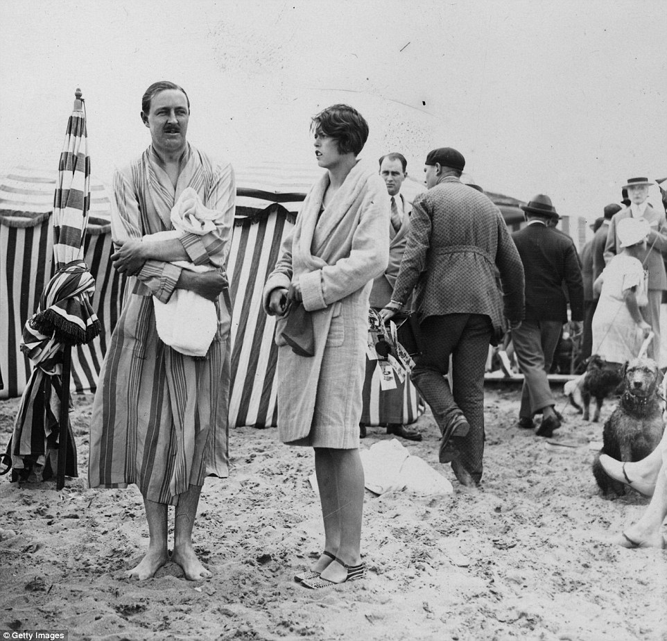 Slide 14 of 25: In the foreground, two people identified as Major Coats and Madame Le Tellier are amongst the fashionable society set holidaying in Deauville in August 1927.