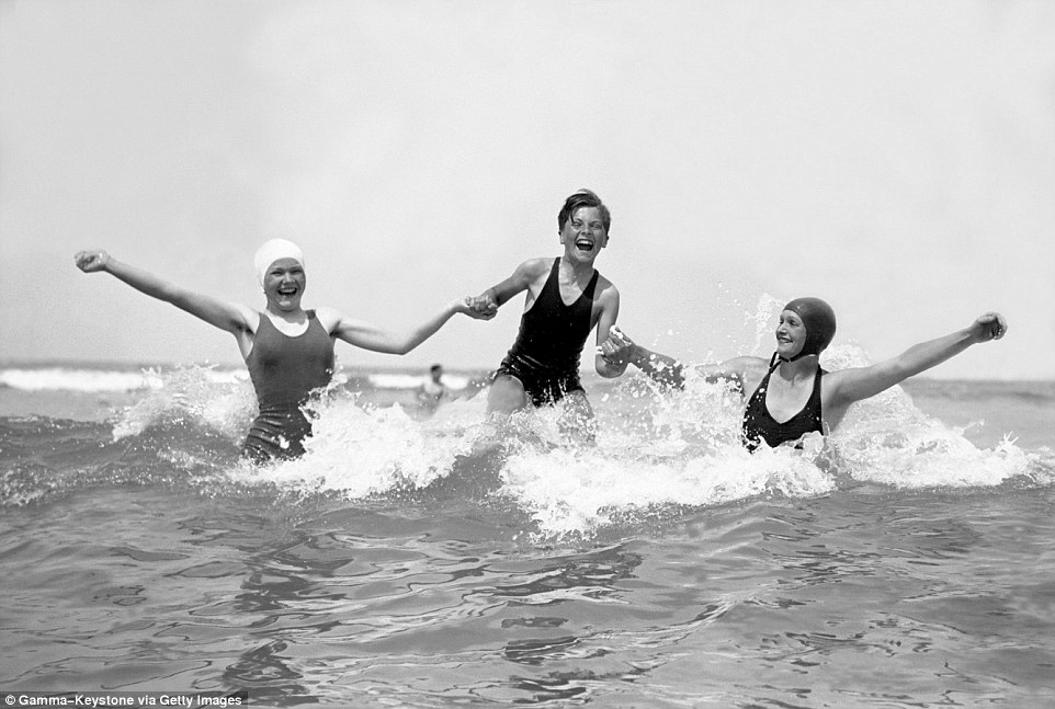 Slide 22 of 25: These three people, pictured above in 1937, look delighted to be splashing around in the calm waters near Deauville Beach.