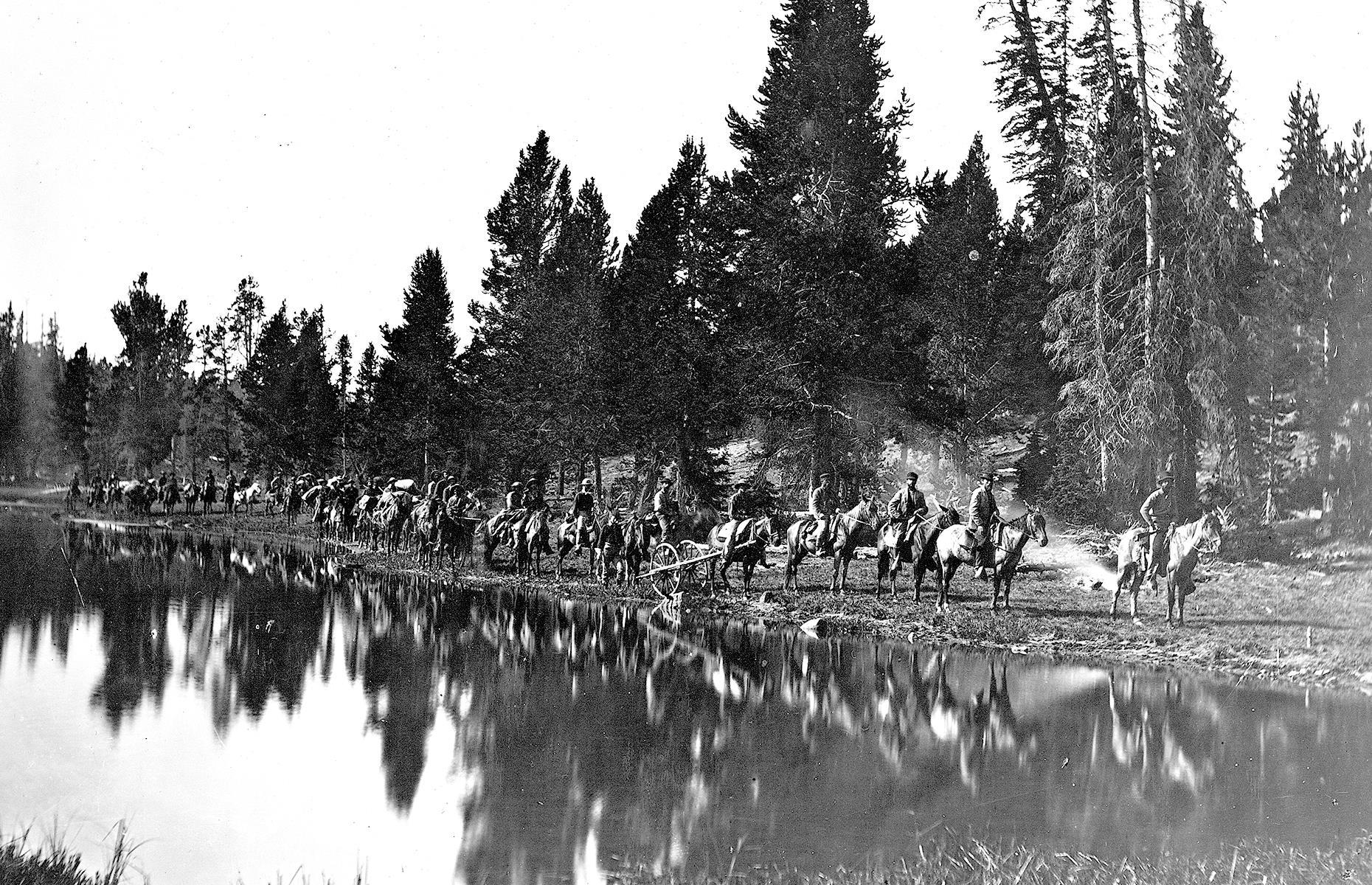 Slide 4 of 51: The first National Park in the US, Yellowstone was established in 1872 and covers a large region in northwestern Wyoming as well as Montana and Idaho. This photograph was captured prior to its official founding and shows men carrying out the Hayden Geological Survey of 1871. Tourists began to visit by rail or horse and carriage from the late 1800s, although it wasn't until cars were allowed in 1915 that tourism really spiked. For thousands of years, Yellowstone has been home to indigenous people and today26 tribes have ties to the area.