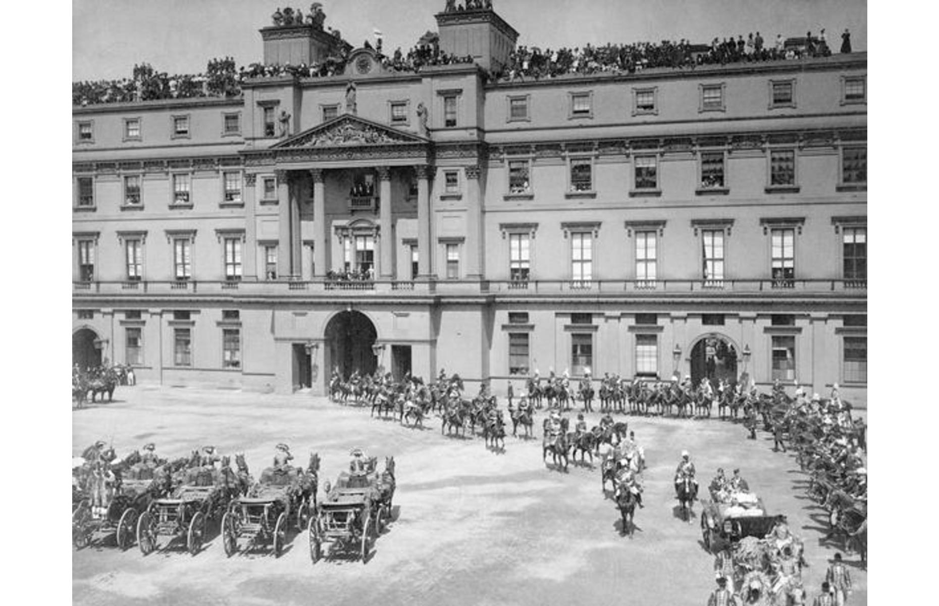 Slide 12 of 51: Shown here during Queen Victoria's Diamond Jubilee in 1897, Buckingham Palace is one of the UK's most famous landmarks and has served as an official residence of the Royal Family since 1837, remaining the administrative headquarters of the Queen today. The palace, which has 775 rooms and is set among 39 acres of grounds, has held public tours every summer since 1993. Another popular event with visitors is the daily Changing of the Guards ceremony outside the Palace gates, although it is currently suspended due to COVID-19.