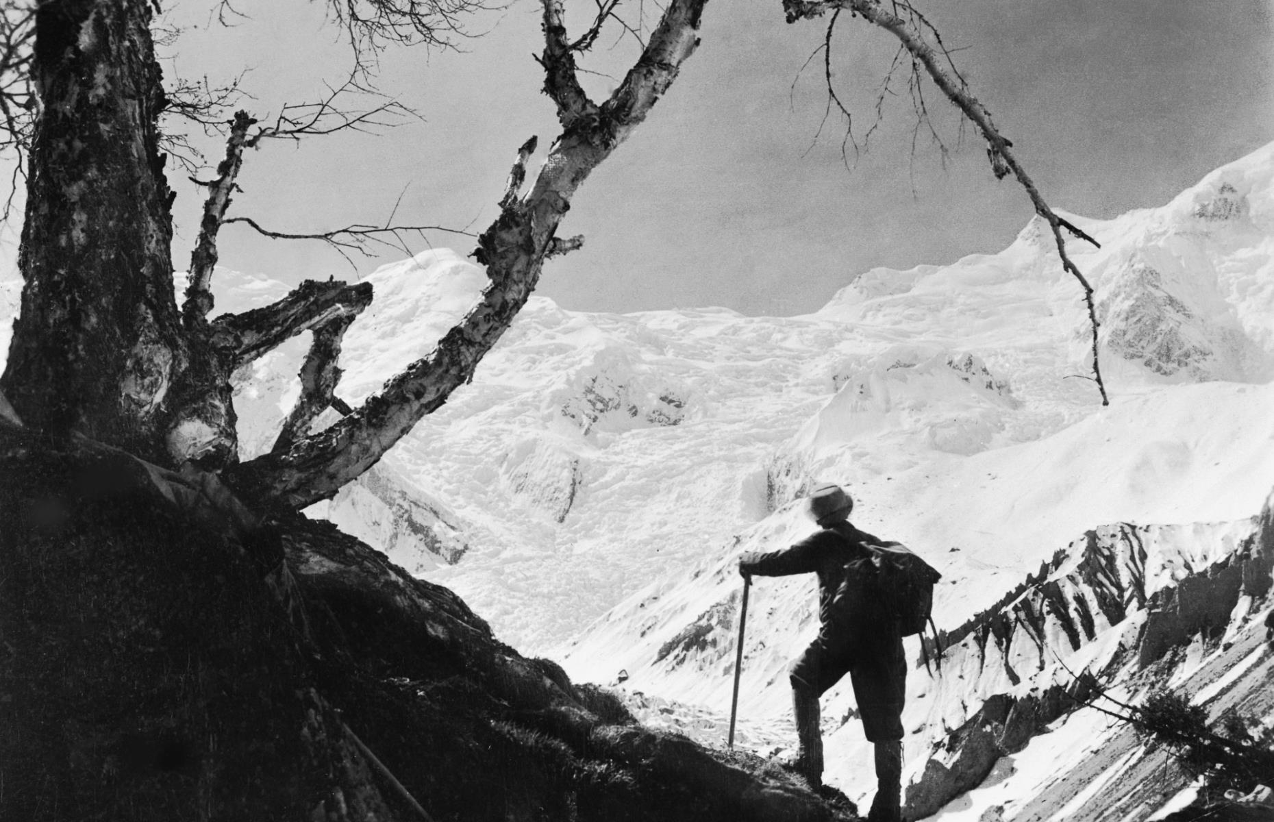 Slide 35 of 51: The tallest mountain on the planet has fascinated people for millennia, but its summit wasn't successfully reached until 1953, when New Zealander explorer Edmund Hillary and Nepali Sherpa Tenzing Norgay officially scaled the peak. Shown here in 1955, a climber gazes out at Mount Everest from one of the surrounding paths. However, overcrowding of the path towards the summit in recent years, fueled in part by cut-price expeditions from Nepali trekking companies, has led to growing concerns about safety. The 2019 season was the deadliest on record, with 11 fatalities.