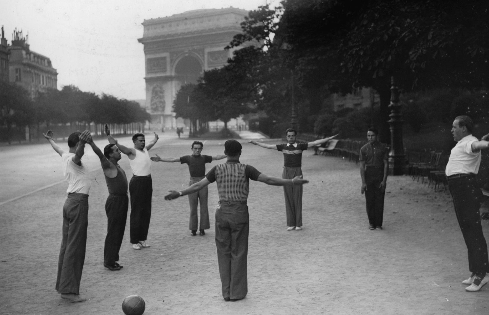 Slide 23 of 51: This striking photograph from the 1920s shows a group of men taking part in an outdoor exercise class next to the Arc de Triomphe – an activity you might have difficulty with during peak season nowadays! The iconic arch was commissioned by Napoleon I in 1806, intended to celebrate the victories of the French army in the Battle of Austerlitz (1805) and it took 30 years to build.