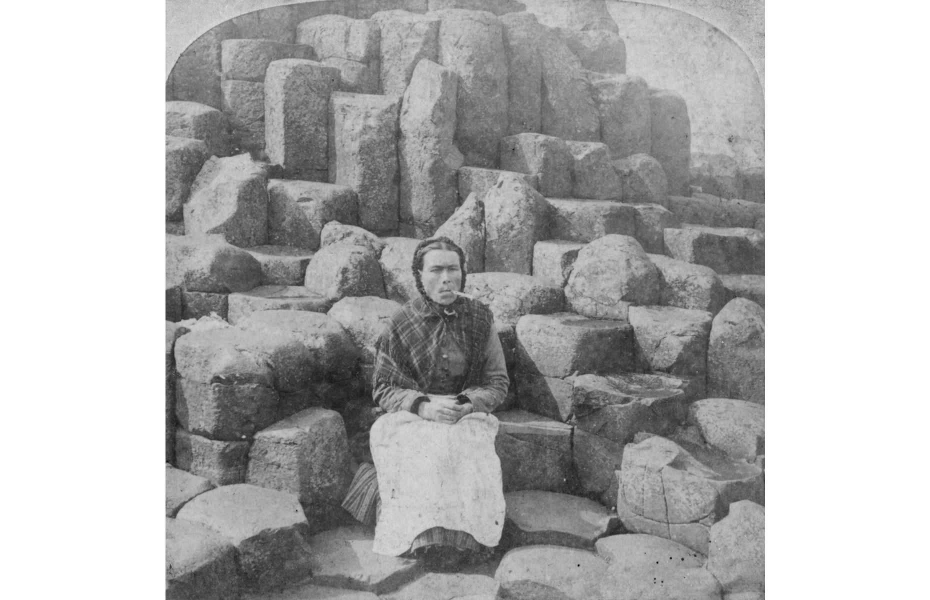 "Slide 5 of 51: The striking basalt columns of the Giant's Causeway in County Antrim, Northern Ireland, were formed by volcanic activity around 50 to 60 million years ago. It gained wider recognition when politician Sir Richard Bulkeley gave a presentation to the Royal Society in 1693 and became popular with wealthy Victorian tourists during the 1800s. The opening of the Causeway Hotel in 1836 drew more visitors to the site. This photograph from 1887 shows a woman sat at the ""Wishing Chair"", a set of columns that form a perfect seat, which is so popular today that the stones have become smooth and shiny."