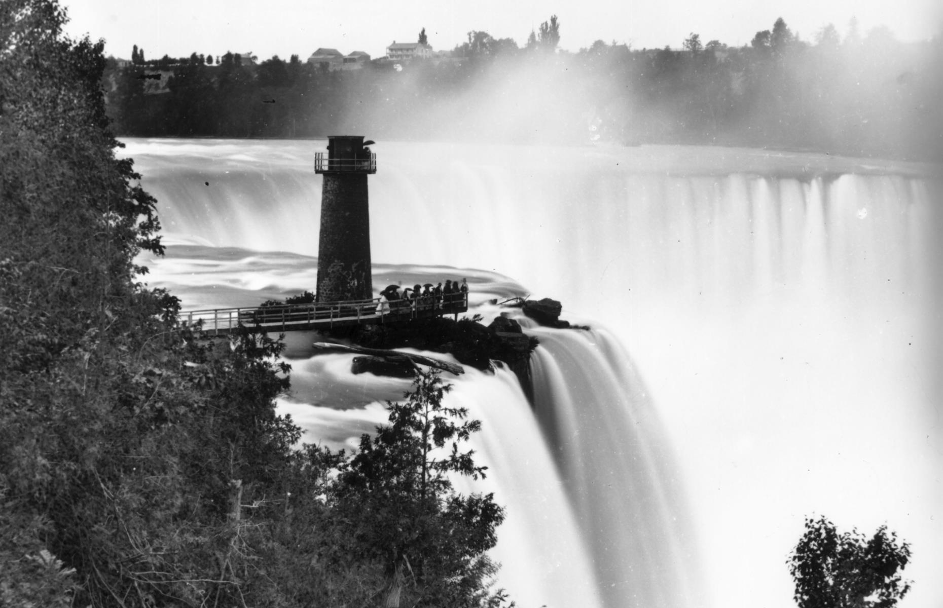 Slide 2 of 51: The gushing great waterfall hasalways fascinated its onlookers, and back in 1859it was no different. Look closely and you can see a small crowd of tourists standing beneath Terrapin Tower, built in 1833 at the edge ofHorseshoe Falls (the Canadian section). A wooden bridge was constructed earlier in 1827 for people to drink in the incredible views across the water. The bridge was an instant hit and attracted visitors from both America and Europe, before tightrope artist Blondin's famous performances over the falls in 1859helped catapult the attraction to further international fame.