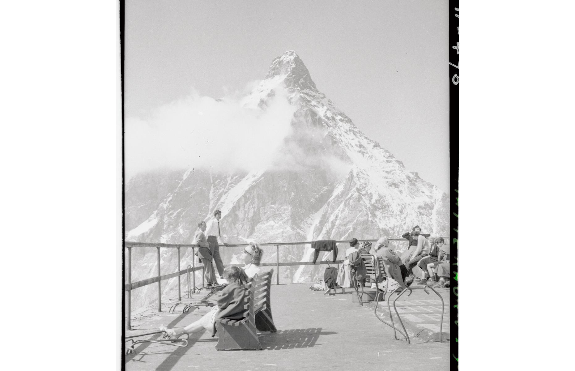 Slide 32 of 51: This horn-shaped mountain in the Swiss Alps, sixmiles (10km) southwest of Zermatt, gained global recognition when its summit was first conquered by British explorer Edward Whymper on 14 July 1865. Tragically however, four of his party fell to their deaths on the way down. In 1971, Whymper published a book about his experience climbing the mountain, Scrambles Among the Alps, which became a global bestseller and sent tourists flocking to the Matterhorn. Pictured here are vacationerson a viewpoint on the Italian side of the mountain in the 1950s.