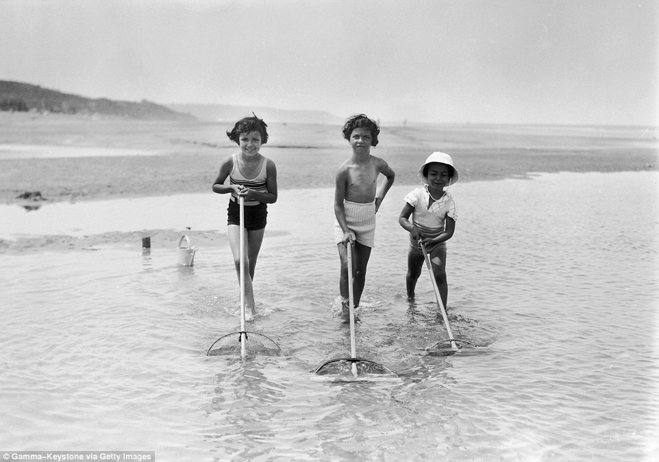 Slide 23 of 25: Three girls are pictured here in 1937, running their nets through the water to catch any fish that might be lurking in shallow waters.
