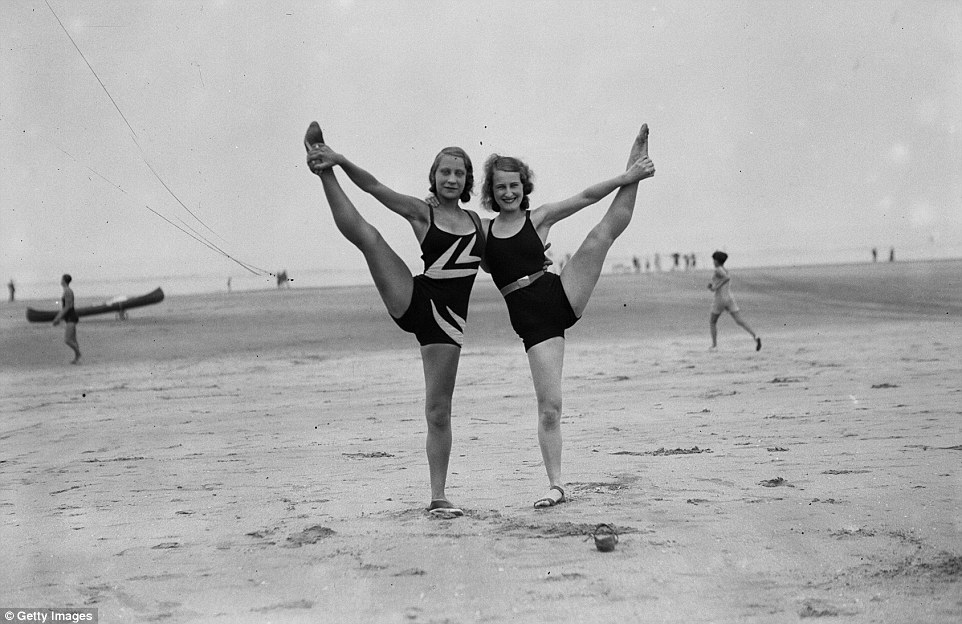 Slide 19 of 25: Fun and games: Two holidaymakers frolic on a relatively empty beach in August 1931.