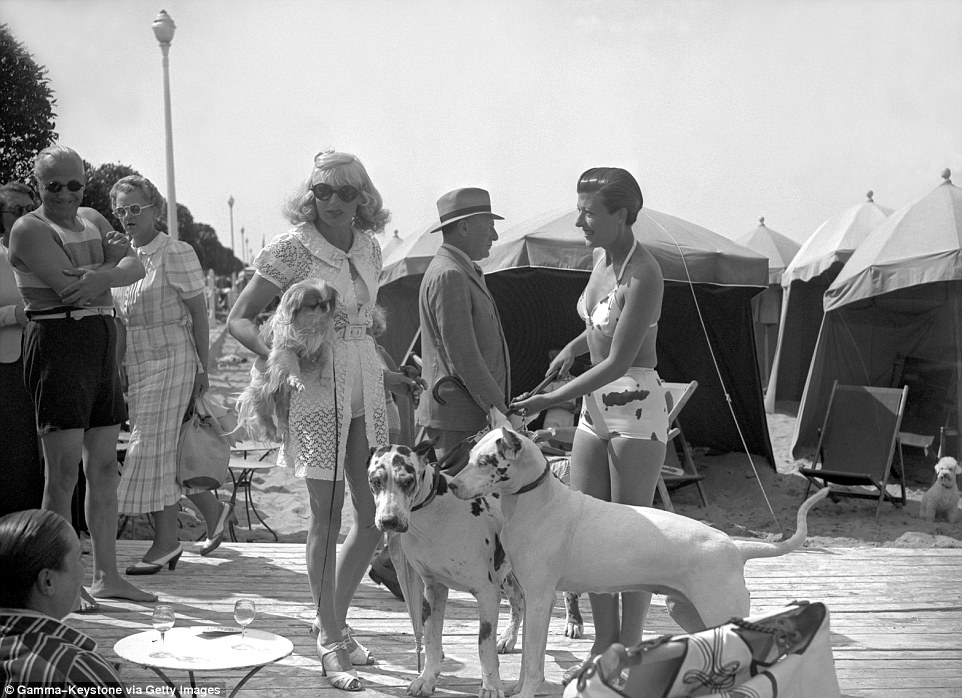 Slide 25 of 25: Countess of Bremond D'Ars holds two dog leads (right) with princess Natacha Sandroff (left) who is carrying her pet, pictured together in 1938.
