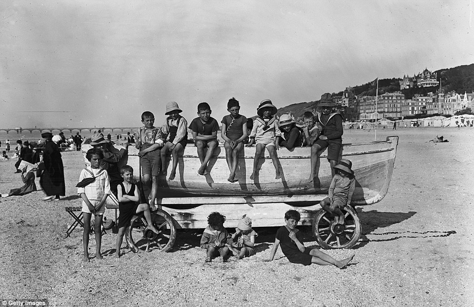 Slide 7 of 25: Despite the gravel on this section of the beach, these children, pictured in September 1919, are happy to go without shoes as they play.